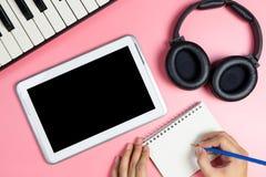 El compositor de la música está escribiendo en un cuaderno con la pantalla en blanco de la tableta Imágenes de archivo libres de regalías