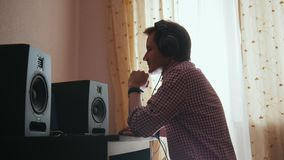 El compositor del hombre joven compone la música en el ordenador, funcionamiento del ingeniero de sonido almacen de video