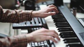 El compositor moderno escribe la música, jugando en un sintetizador electrónico almacen de video