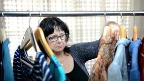 El comprador de mediana edad de la mujer descubre que una blusa en el estante de la ropa es sucia almacen de metraje de vídeo