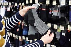 El comprador del hombre elige calcetines en tienda Fotografía de archivo libre de regalías