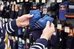 El comprador del hombre elige calcetines en tienda Fotos de archivo libres de regalías