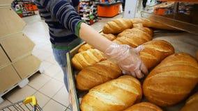 El comprador elige el pan fresco en un supermercado almacen de video