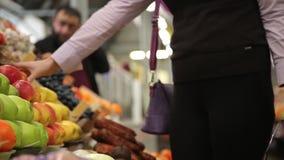 El comprador elige las manzanas en el mercado y añade a metrajes
