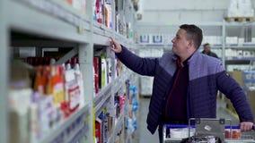 El comprador elige las mercancías del contador almacen de metraje de vídeo