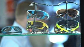 El comprador elige los nuevos lentes de sol en la tienda almacen de video
