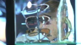 El comprador elige los nuevos lentes de sol en la tienda metrajes