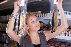 El comprador elige pescados fumados Imagen de archivo libre de regalías