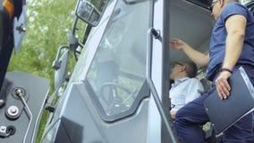 El comprador examina la cabina del ` s del tractor desde adentro en salón del aire libre metrajes