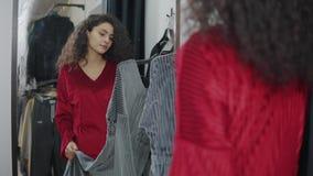 El comprador femenino está comparando dos diversos colores del vestido en vestuario almacen de video