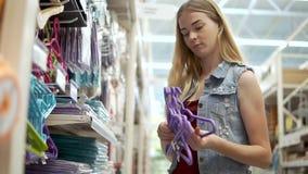 El comprador femenino está eligiendo las suspensiones para la ropa en una tienda, primer metrajes