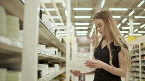 El comprador femenino está mirando la placa de cerámica blanca en un pasillo del supermercado almacen de metraje de vídeo