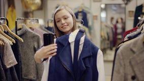 El comprador femenino joven alegre intenta encendido un vestido y toma las fotos de ella misma con él en cámara del smartphone en metrajes