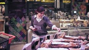 El comprador femenino joven escoge algún producto de carne preembalado en un colmado metrajes