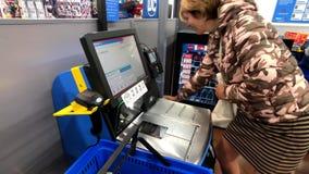 El comprador femenino utiliza el terminal del autoservicio en el supermercado de Walmart metrajes