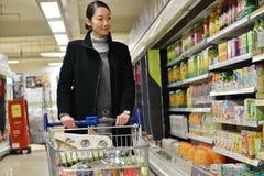 El comprador hojea un pasillo del supermercado Imagen de archivo