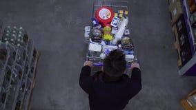 El comprador lleva un carro del ultramarinos en el supermercado almacen de video