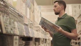 El comprador masculino está examinando el catálogo de producto de la teja para los trabajos de acabado en casas almacen de video