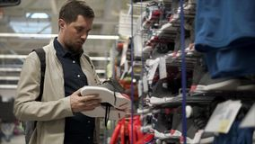 El comprador masculino está mirando pares de zapatillas de deporte en un área de las ventas en tienda del deporte almacen de video