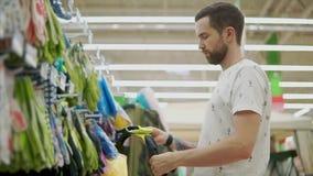 El comprador masculino está sintiendo guantes de goma protectores en manos en hipermercado almacen de metraje de vídeo