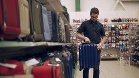 El comprador masculino está tomando la maleta plástica del estante en un supermercado, examinando metrajes