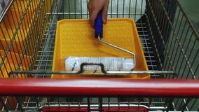 El comprador pone los materiales de construcción y las herramientas de la pintura en el carro de la compra almacen de video