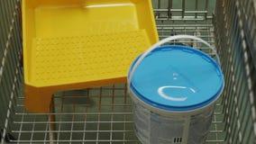 El comprador pone una lata de la pintura, del rodillo y del cepillo en el carro de la compra metrajes