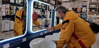 El comprador selecciona los espejos y los gabinetes para el cuarto de baño en la tienda imagen de archivo libre de regalías