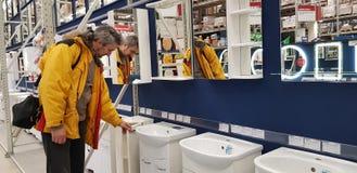 El comprador selecciona los espejos y los gabinetes para el cuarto de baño en la tienda imagenes de archivo
