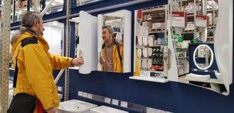 El comprador selecciona los espejos y los gabinetes para el cuarto de baño en la tienda foto de archivo libre de regalías