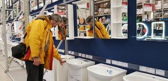 El comprador selecciona los espejos y los gabinetes para el cuarto de baño en la tienda fotos de archivo