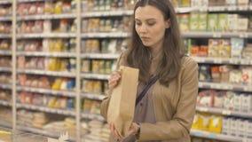 El comprador vierte por peso los guisantes vendidos en la bolsa de papel metrajes