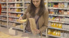 El comprador vierte por peso los guisantes vendidos en la bolsa de papel almacen de video