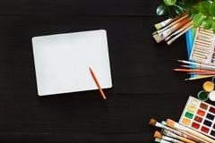 El concepto creativo de la tabla de trabajo de arte, imita encima de las brochas y de la caja de pinturas en blanco del cuaderno imágenes de archivo libres de regalías