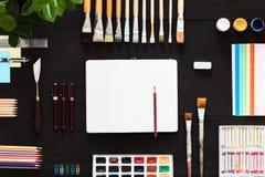 El concepto creativo de la tabla de trabajo de arte, imita encima de las brochas y de la caja de pinturas en blanco del cuaderno imagenes de archivo