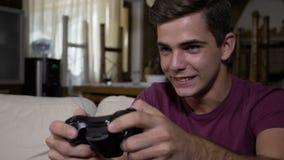 El concepto de adolescente juguetón del apego video extremo del juego en casa que empuja el regulador cierra intentar ganando el  metrajes