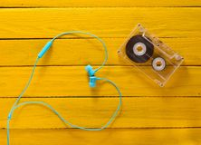 El concepto de amor de la música Auriculares, casete audio en una tabla de madera amarilla fotos de archivo