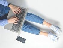 El concepto de blogging, trabajando en un ordenador portátil Usando un ordenador portátil que se sienta en un piso blanco Tecnolo Foto de archivo libre de regalías