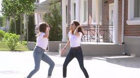 El concepto de buenas noticias dos muchachas baila en la calle después de leer el mensaje metrajes