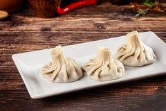 El concepto de cocina georgiana Khinkali de la pasta blanca con la carne Platos de porción en el restaurante georgiano en una pla imagen de archivo libre de regalías