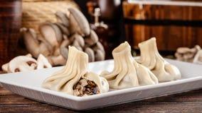 El concepto de cocina georgiana Khinkali de la pasta blanca con las setas Platos de porción en el restaurante georgiano en una pl fotos de archivo