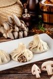 El concepto de cocina georgiana Khinkali de la pasta blanca con las setas Platos de porción en el restaurante georgiano en una pl fotos de archivo libres de regalías