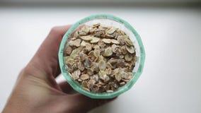 El concepto de cocinero sano del desayuno mira en un vidrio tallado con una mezcla de diversas escamas La mano masculina de la ma almacen de video