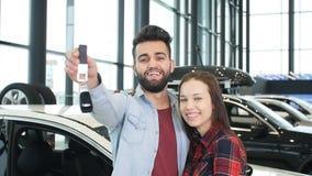 El concepto de comprar o de alquilar un coche Pares interraciales felices jovenes con nuevas llaves del coche almacen de metraje de vídeo
