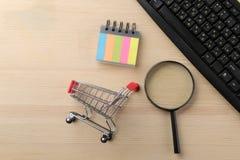El concepto de compras en línea Composición con una lupa y una carretilla que hace compras en el fondo de la tabla imagen de archivo libre de regalías