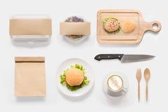 El concepto de diseño de la hamburguesa de la maqueta, de la ensalada y de la taza de café fijó en whi Imágenes de archivo libres de regalías