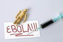 El concepto de Ebola con una figura y una sangre de madera llenó la jeringuilla Fotografía de archivo