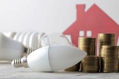 El concepto de electricidad del ahorro dinero, casa decorativa y diversos bulbos en un fondo ligero foto de archivo
