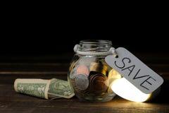 El concepto de electricidad del ahorro Dinero en el banco y bombilla económica en una tabla de madera imagen de archivo libre de regalías