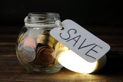 El concepto de electricidad del ahorro Dinero en el banco y bombilla económica en una tabla de madera foto de archivo